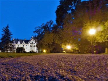 The paths and castle are brightly lit at night.
