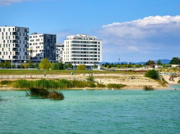 Green water, modern highrise apartment blocks, and a view of the Donauturm at Seestadt Aspern