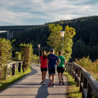 Red, blue and green - joggers frequent the walkway around the Wienerwaldsee.