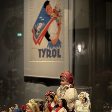 Costumed dolls and an advertisement for Tyrol featuring fashionable head scarfs